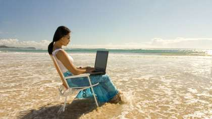 Woman sitting on the beach while working on her laptop.